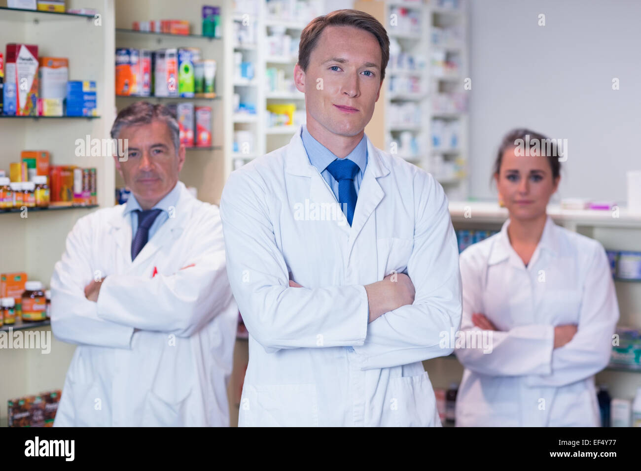 Smiling pharmacy team standing with arms folded - Stock Image