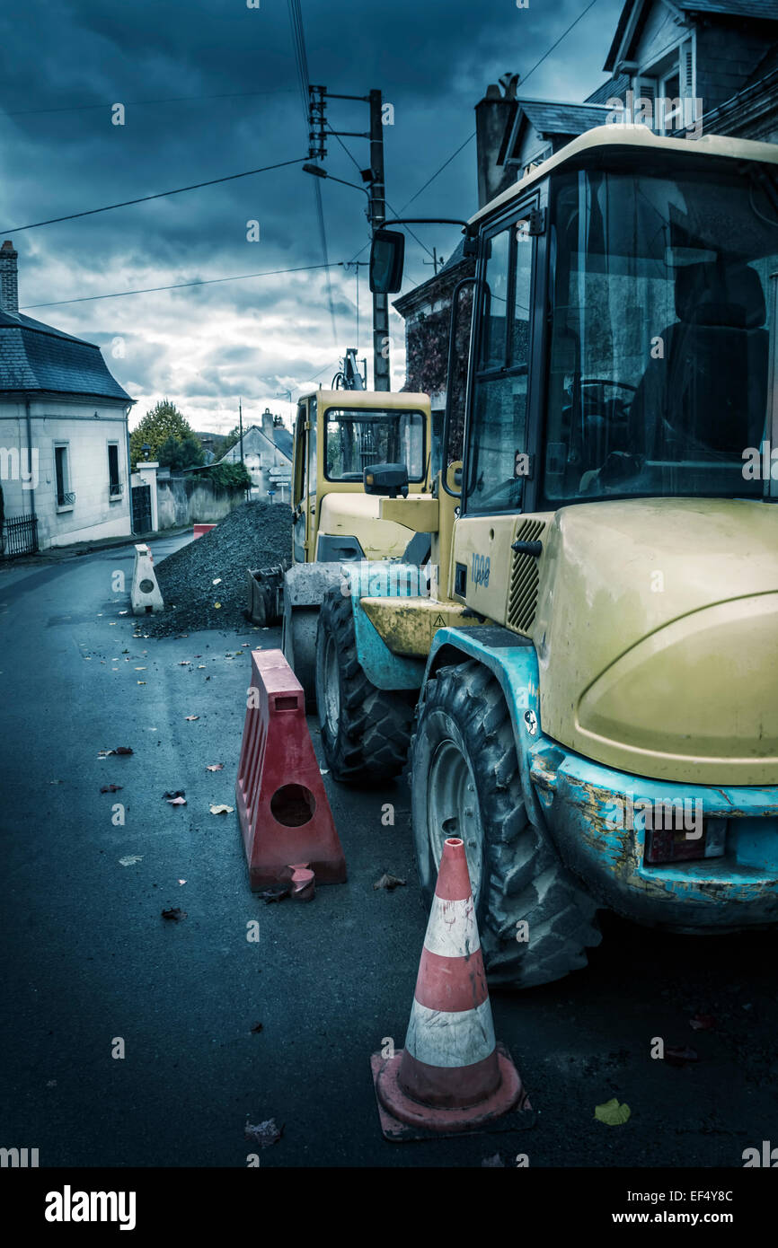 Two construction vehicles parked on the street. - Stock Image
