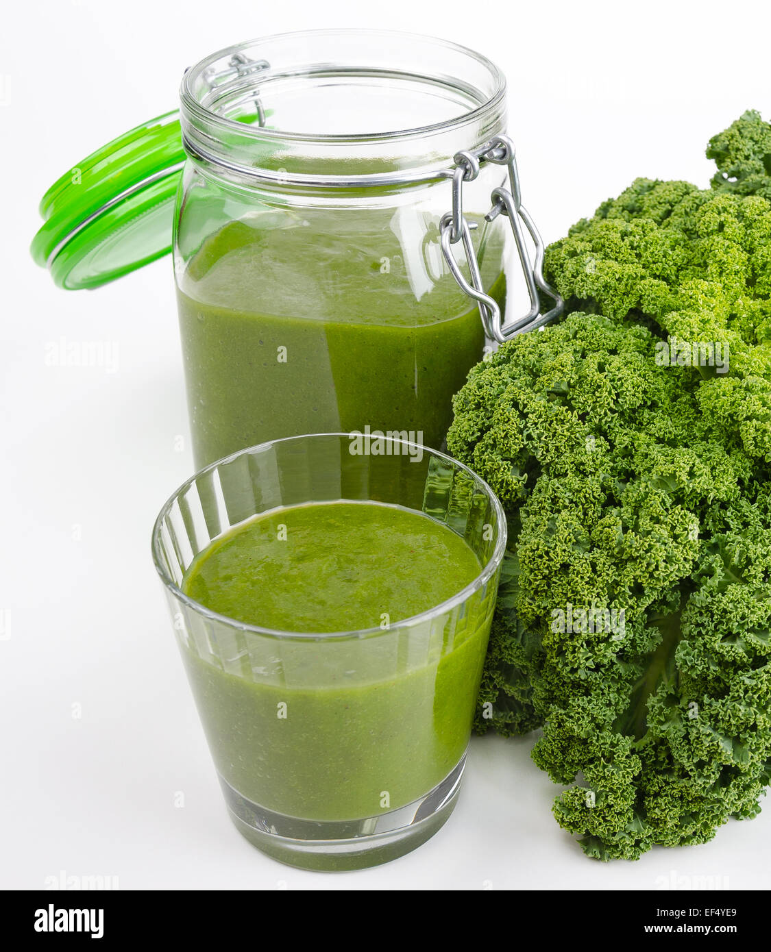 Green smoothie in a glass and in a open jar with fresh kale. A raw, healthy and vegan beverage made of green leafs - Stock Image