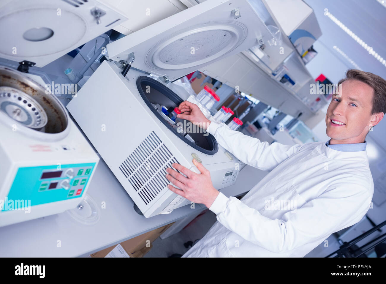 Smiling chemist using a centrifuge looking at camera - Stock Image