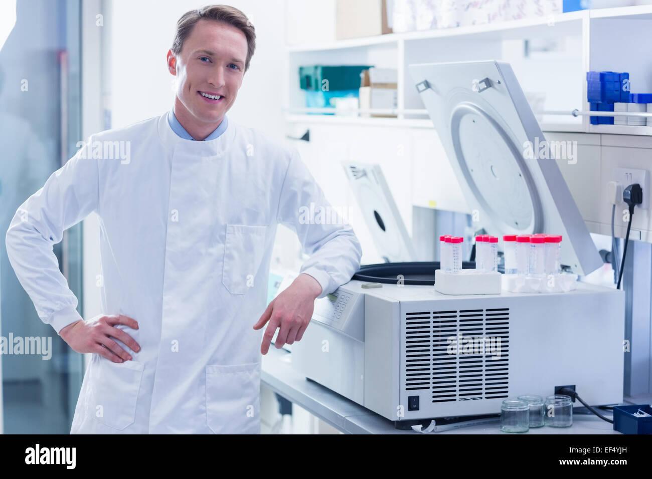 Smiling chemist leaning against the centrifuge - Stock Image