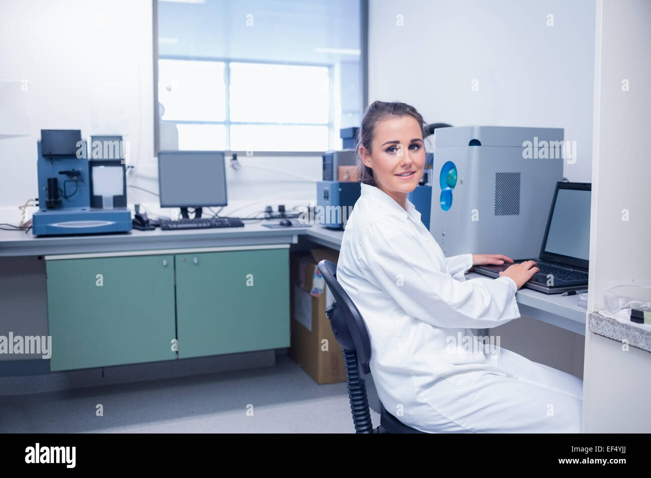 Smiling young biochemist using laptop at her desk Stock Photo