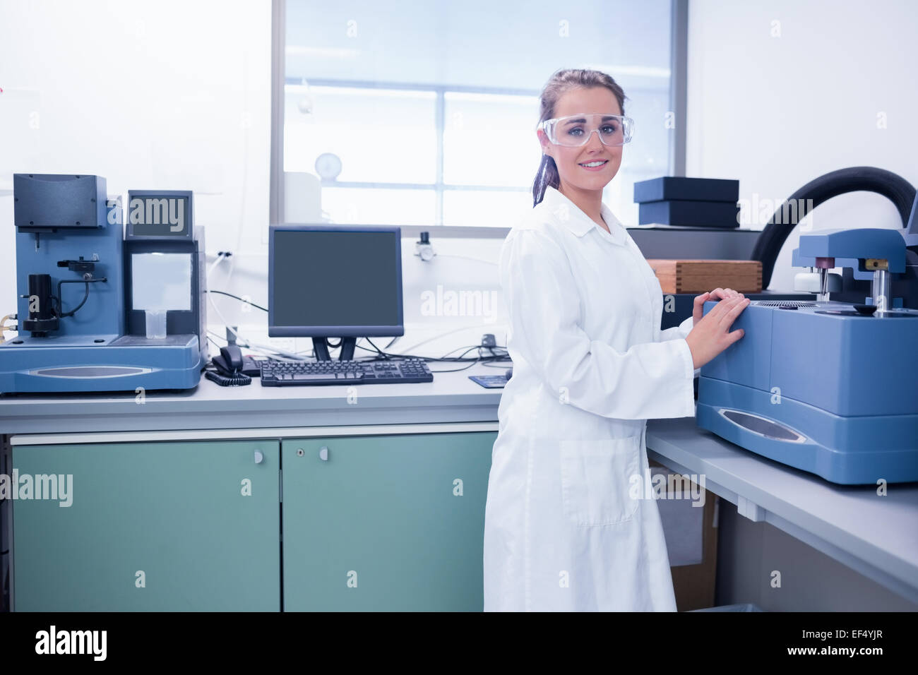 Young chemist with safety glasses doing scientific research - Stock Image