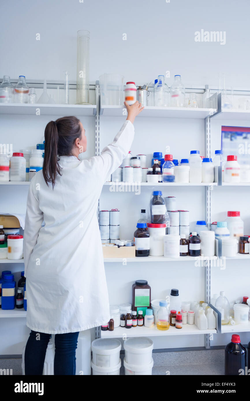 Young chemist taking container from shelf - Stock Image