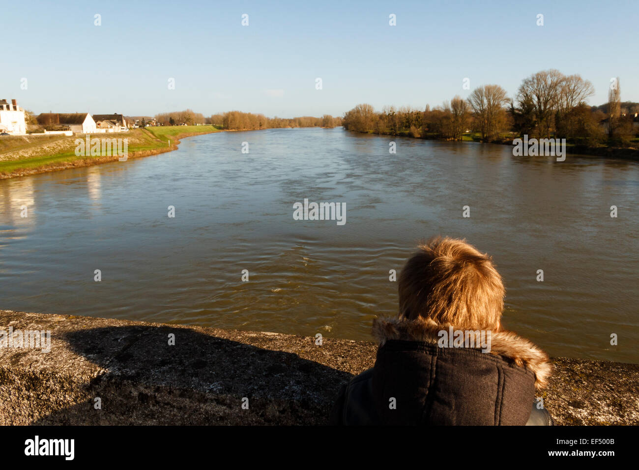 Young boy outdoors looking at water, river Loire, France. - Stock Image