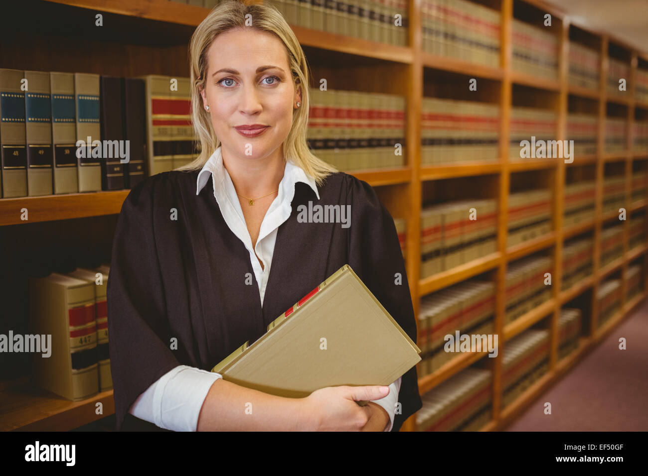 Serious lawyer holding a file while standing - Stock Image