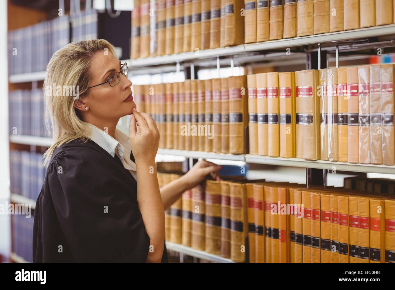 Lawyer wearing glasses and looking for a book in the shelf - Stock Image