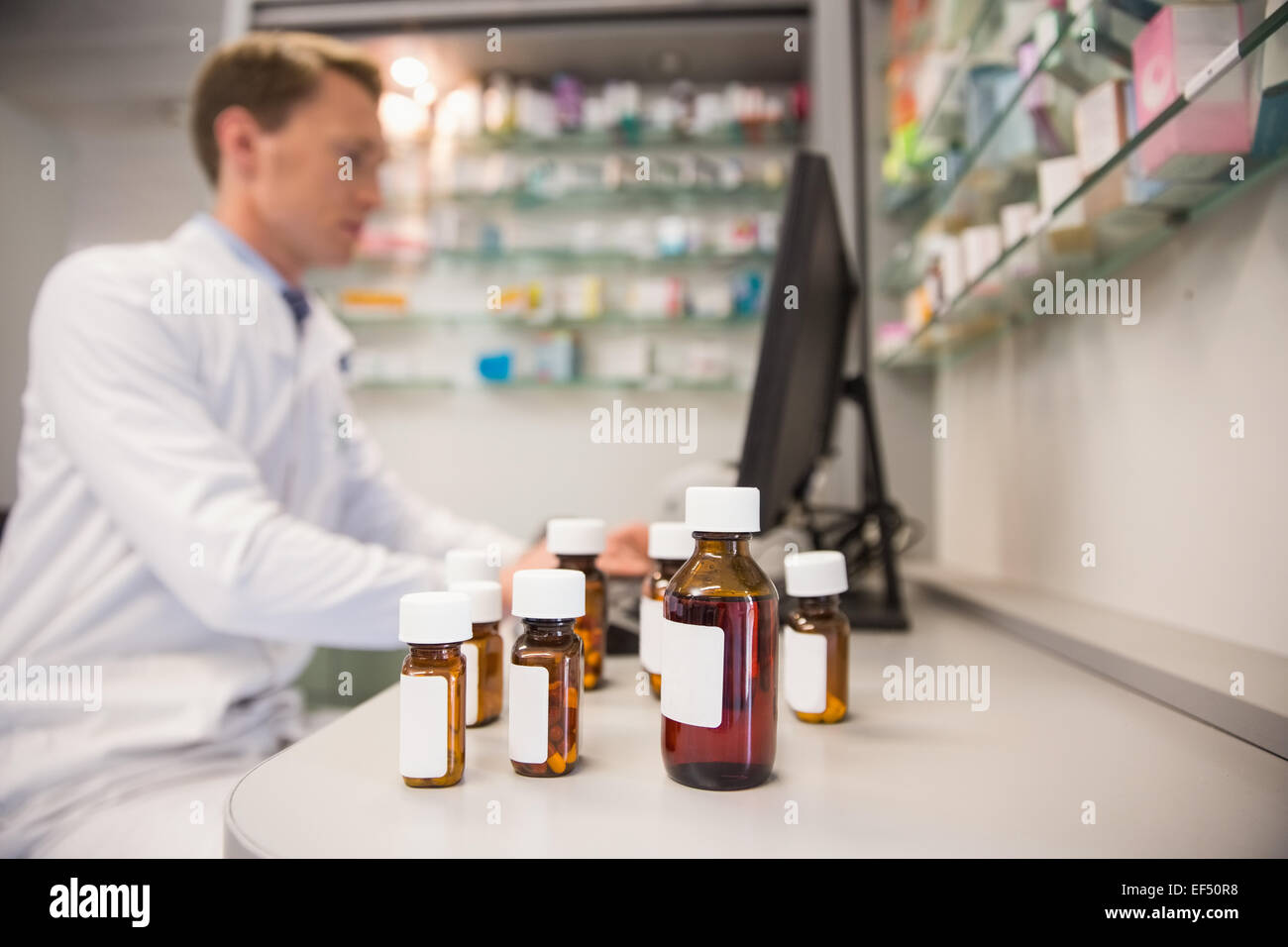Pharmacist using computer at desk - Stock Image