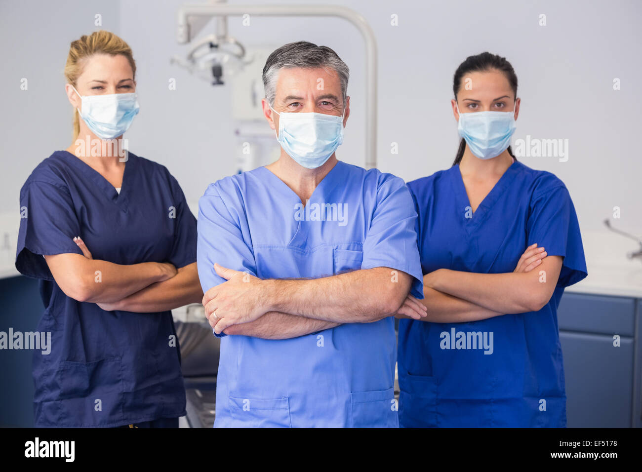 Co-workers wearing surgical mask with arms crossed - Stock Image