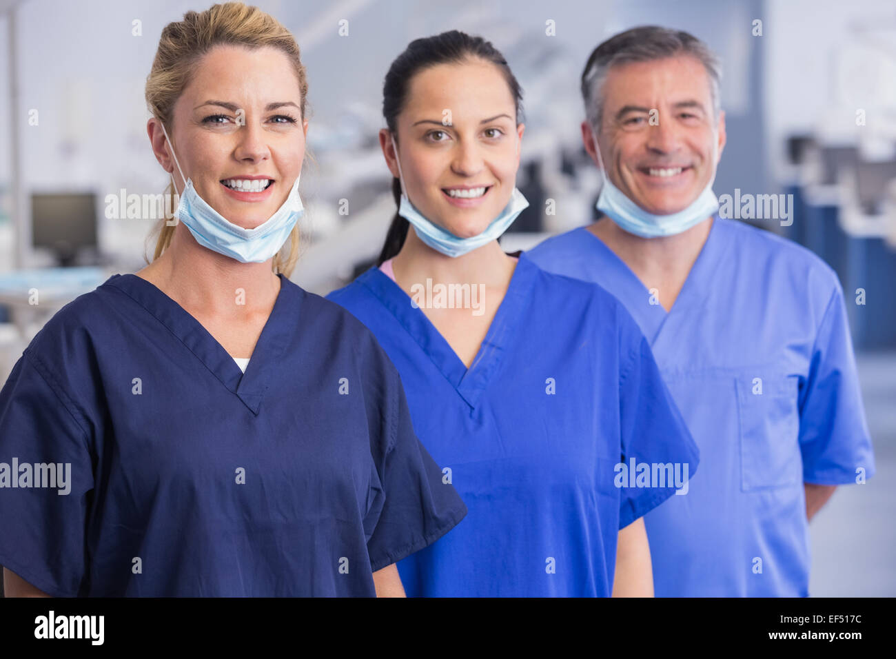 Portrait of smiling co-workers standing in a line - Stock Image
