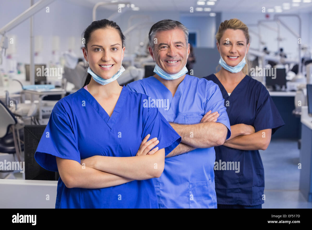Portrait of smiling co-workers in a line with arms crossed - Stock Image