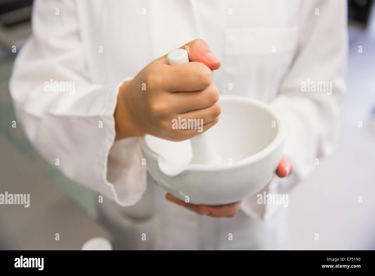 Junior pharmacist mixing a medicine - Stock Image