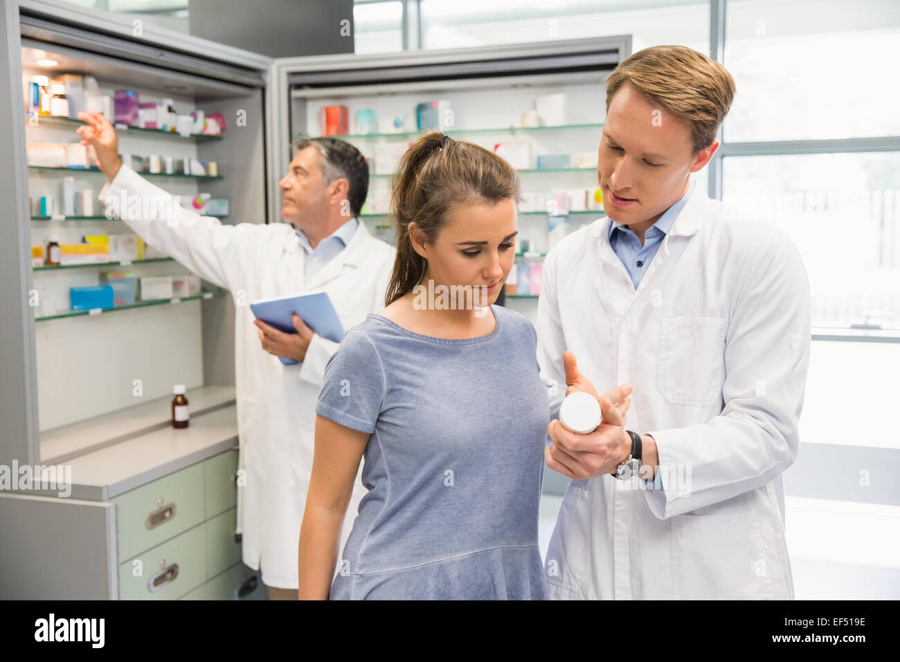 Happy customer talking with pharmacist - Stock Image