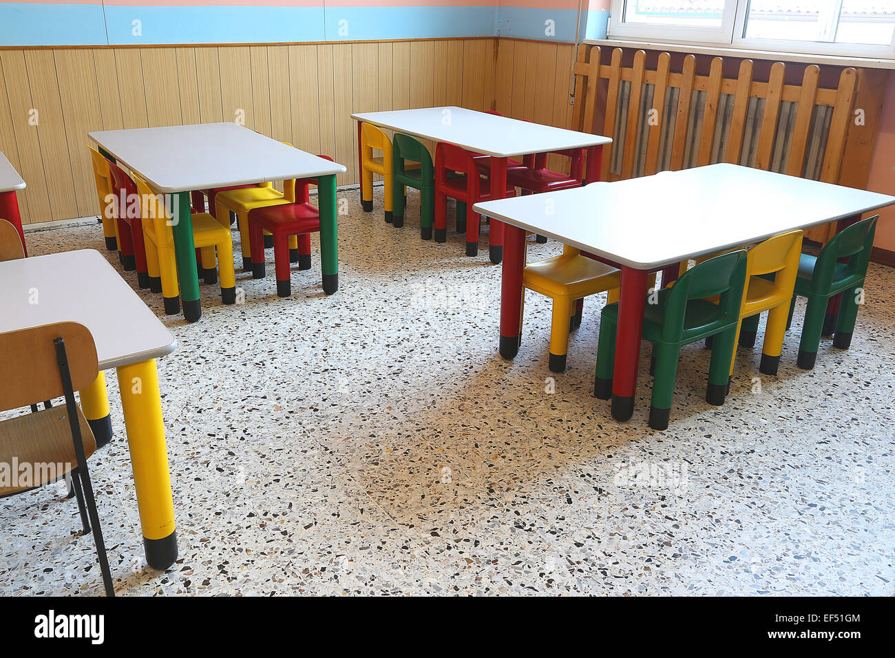 colored plastic chairs and small tables of school refectory for