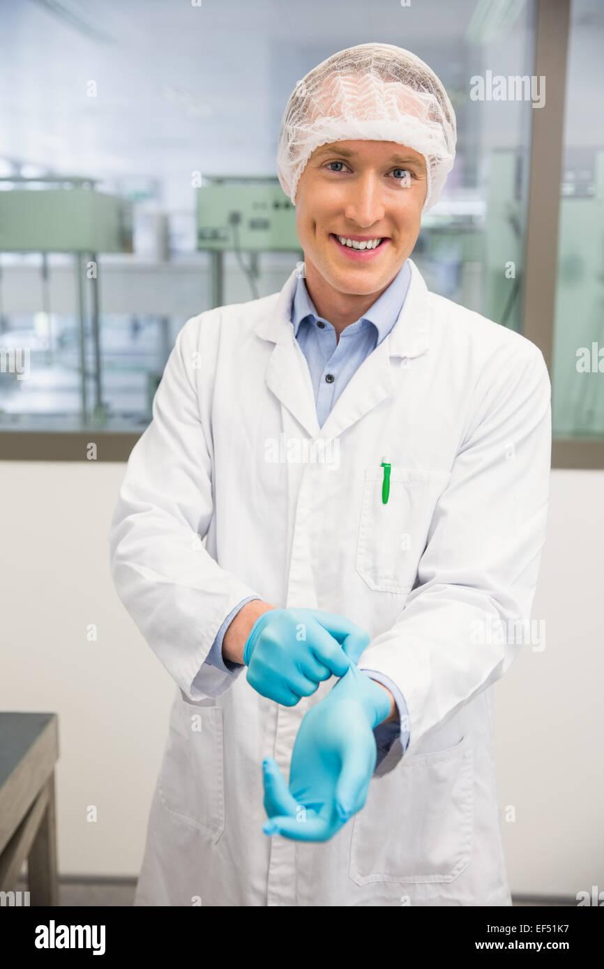 Pharmacist pulling on rubber gloves - Stock Image