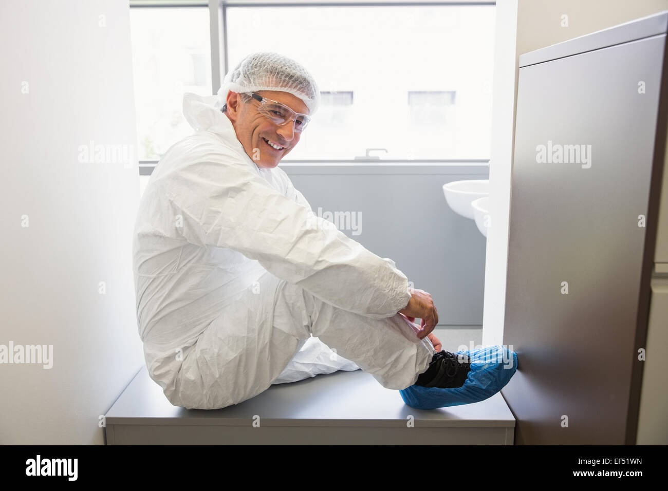 Pharmacist putting on his shoe covers Stock Photo