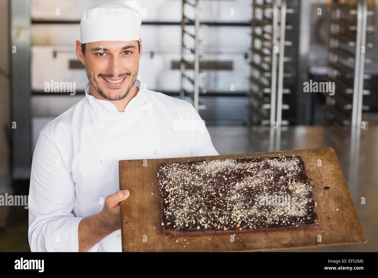 Baker showing freshly baked brownie - Stock Image