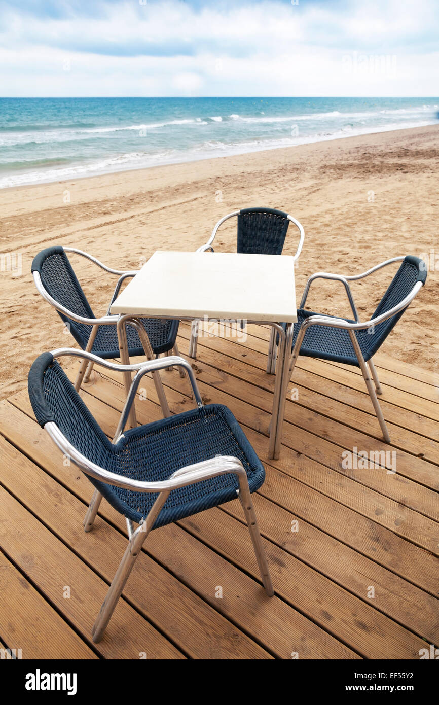 Open Space Seaside Bar Interior With Wooden Floor And Metal Armchairs On  The Sandy Beach