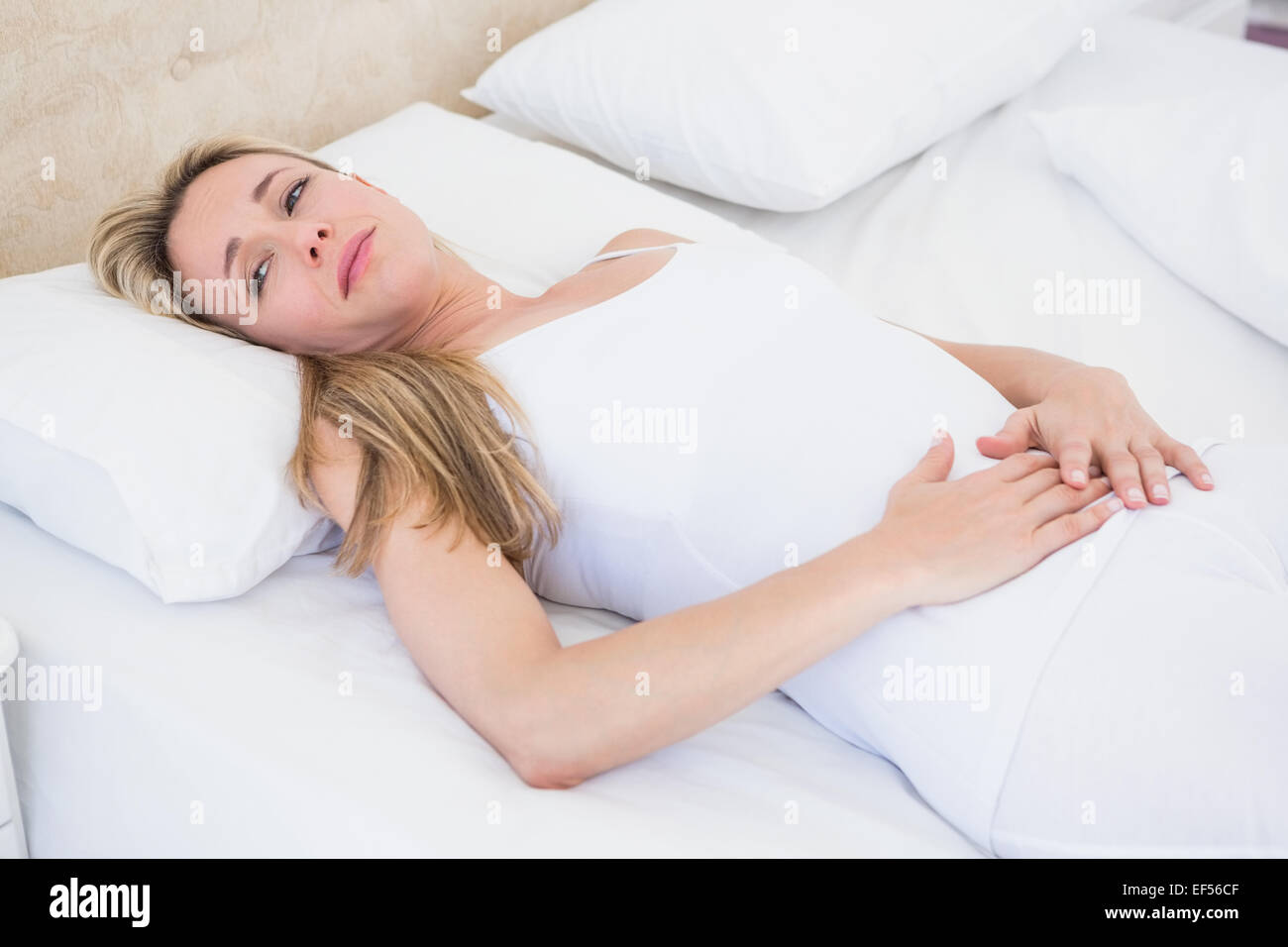 Grimacing woman suffering with stomach pain - Stock Image