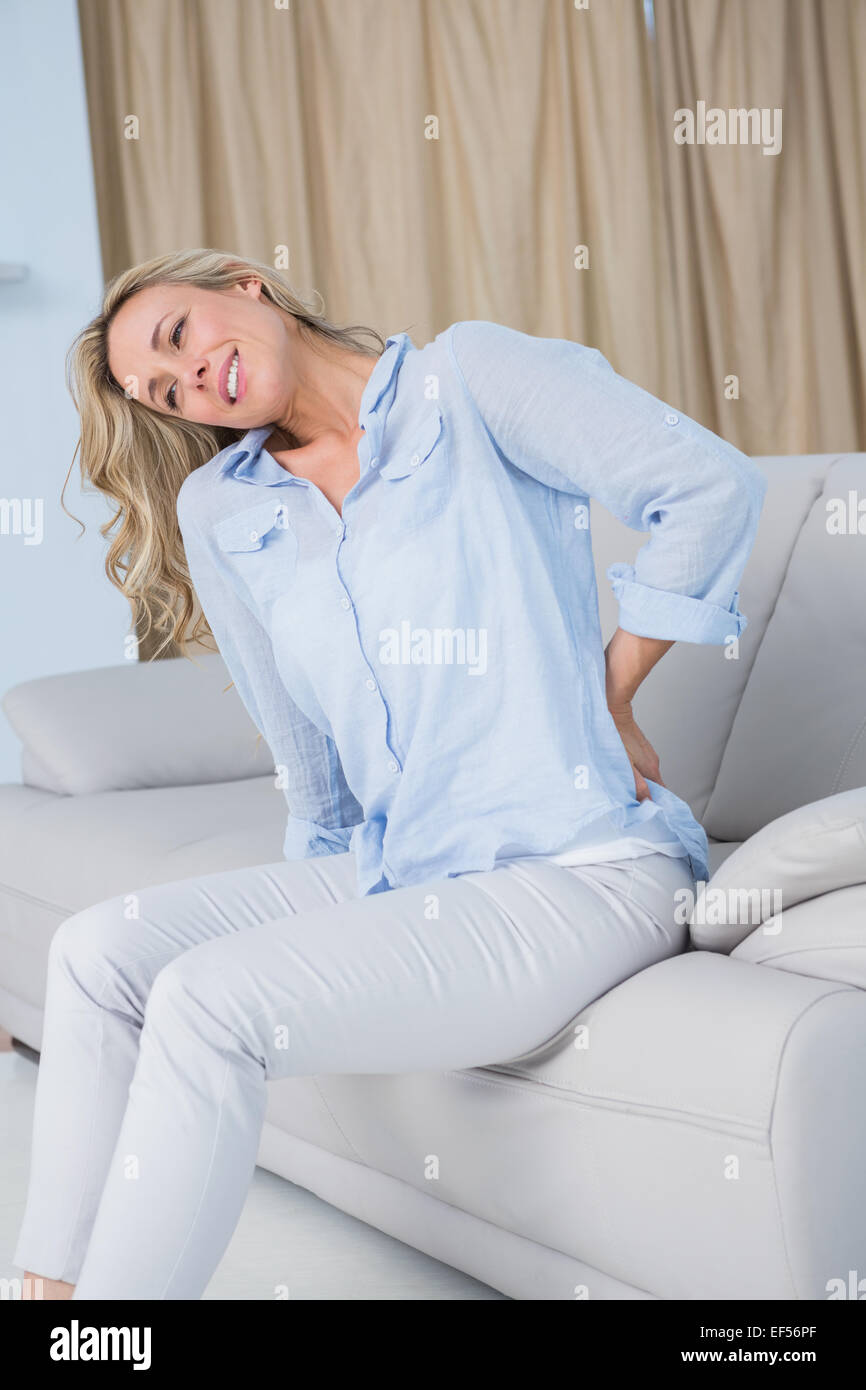 Grimacing blonde getting back pain - Stock Image