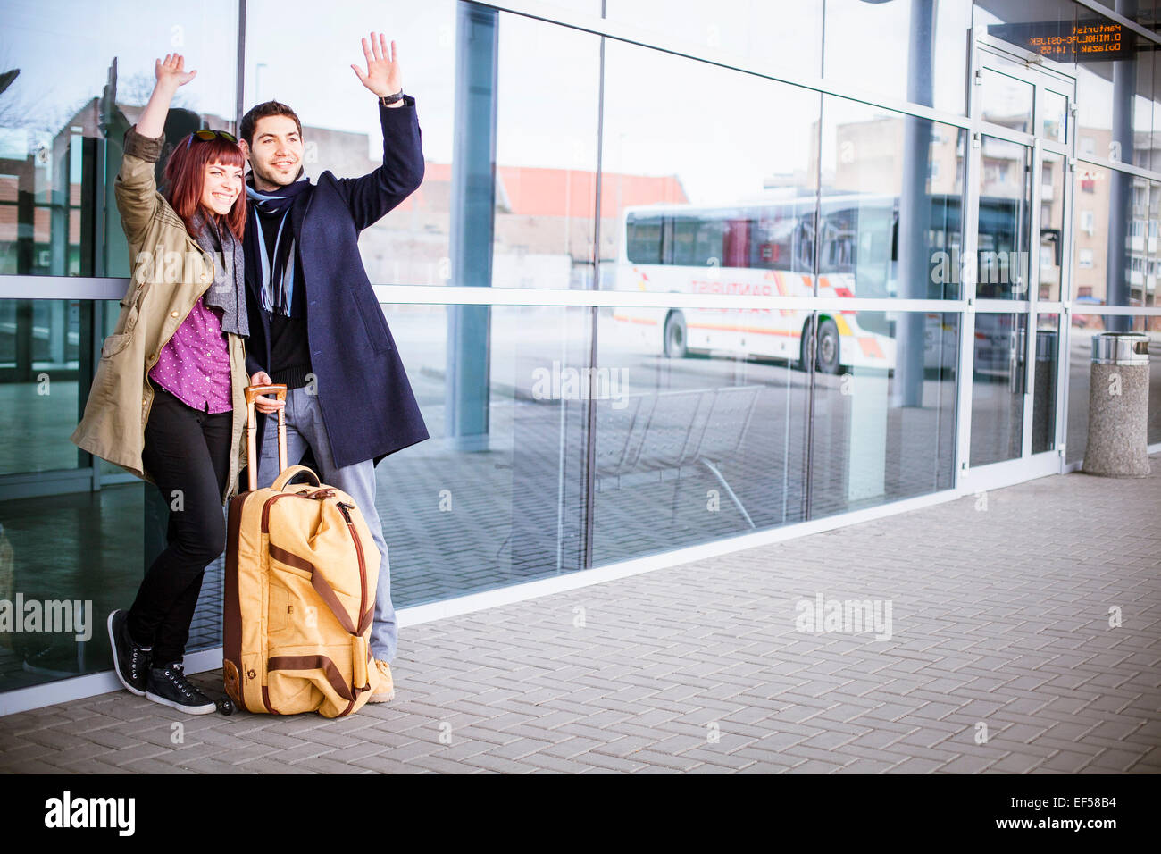 Happy young couple with luggage by airport building - Stock Image