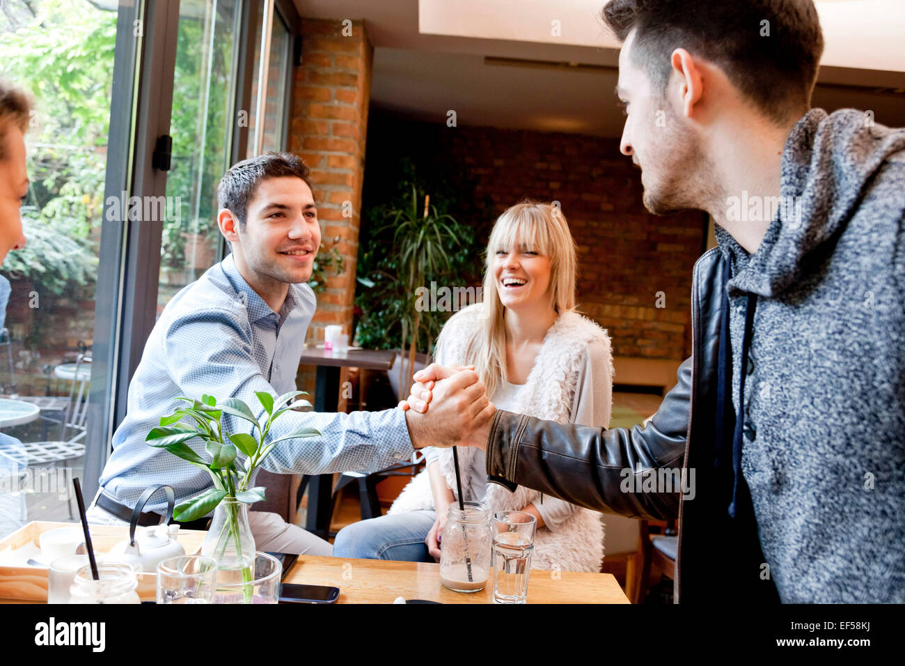 Friends shaking hands at home - Stock Image