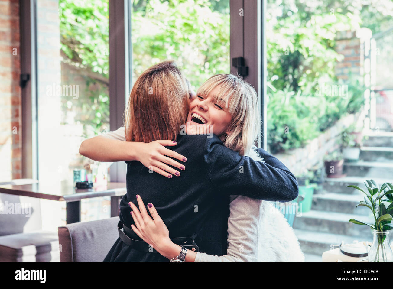 Two young women embracing happily - Stock Image