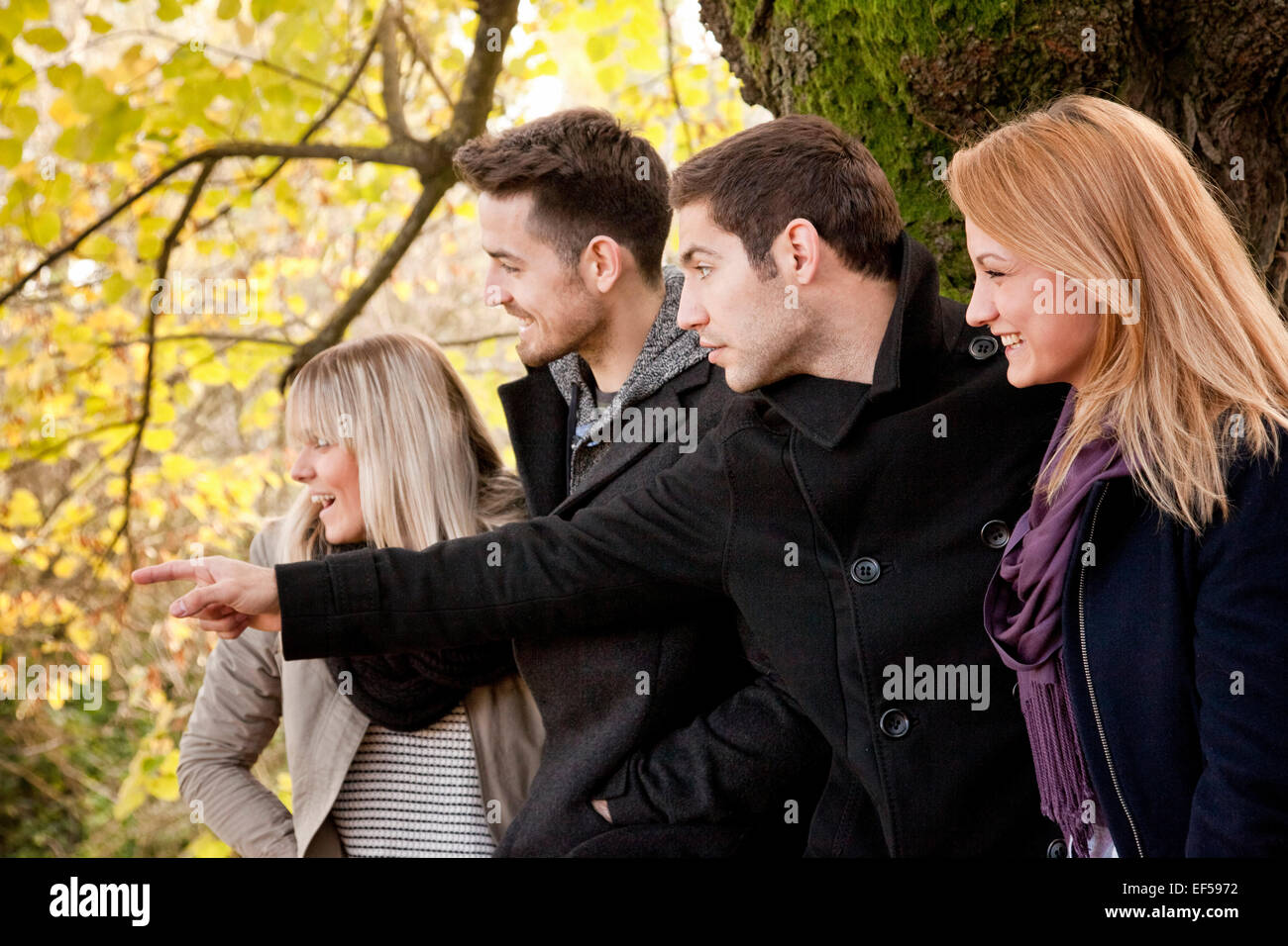 Group of friends, man pointing with hand - Stock Image