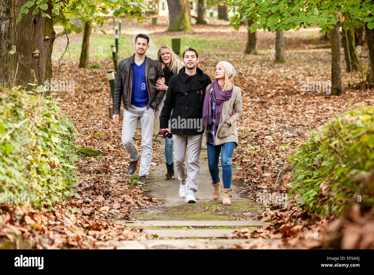 Group of friends walking through autumn park - Stock Image