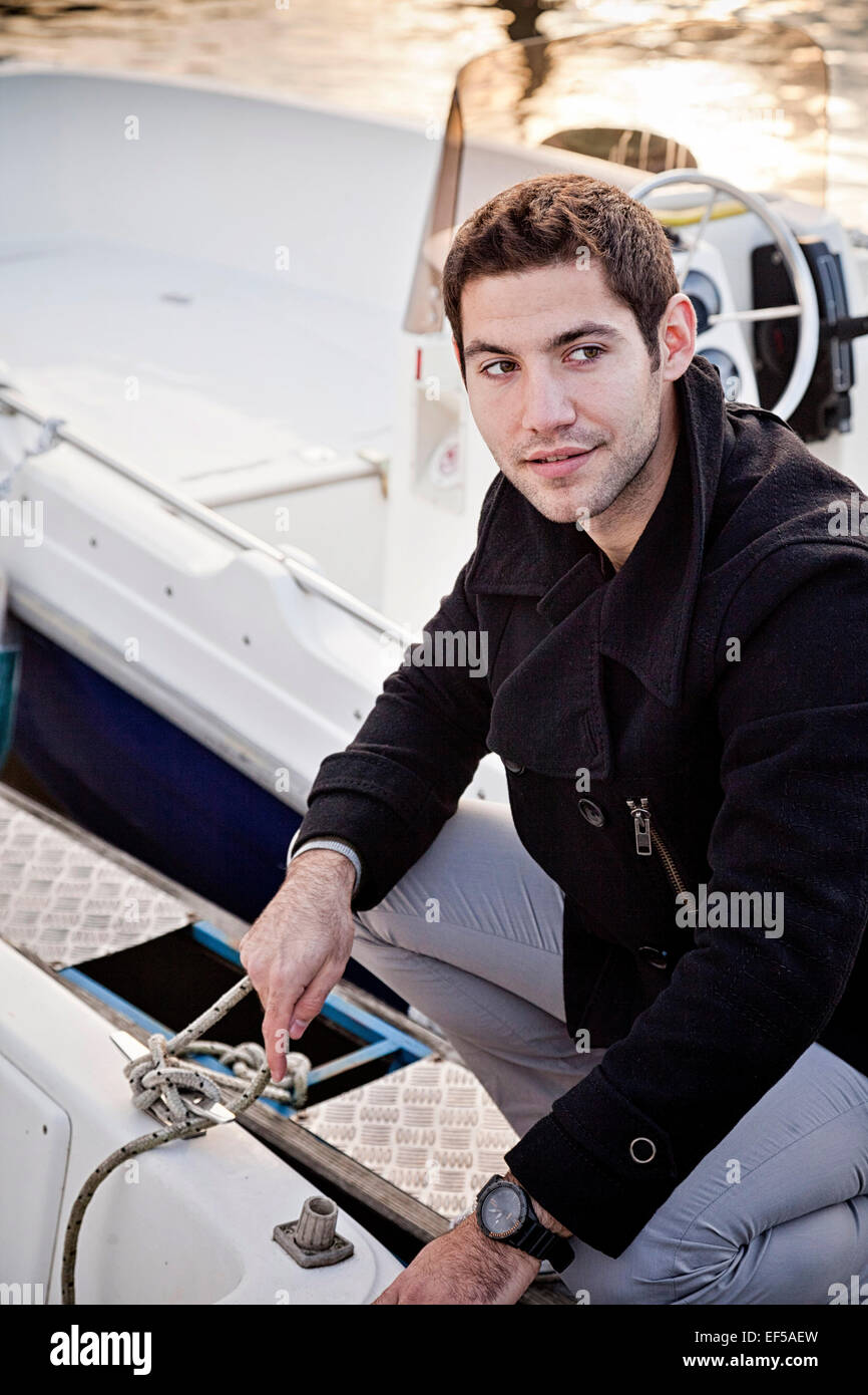 Young man tying rope of motorboat - Stock Image