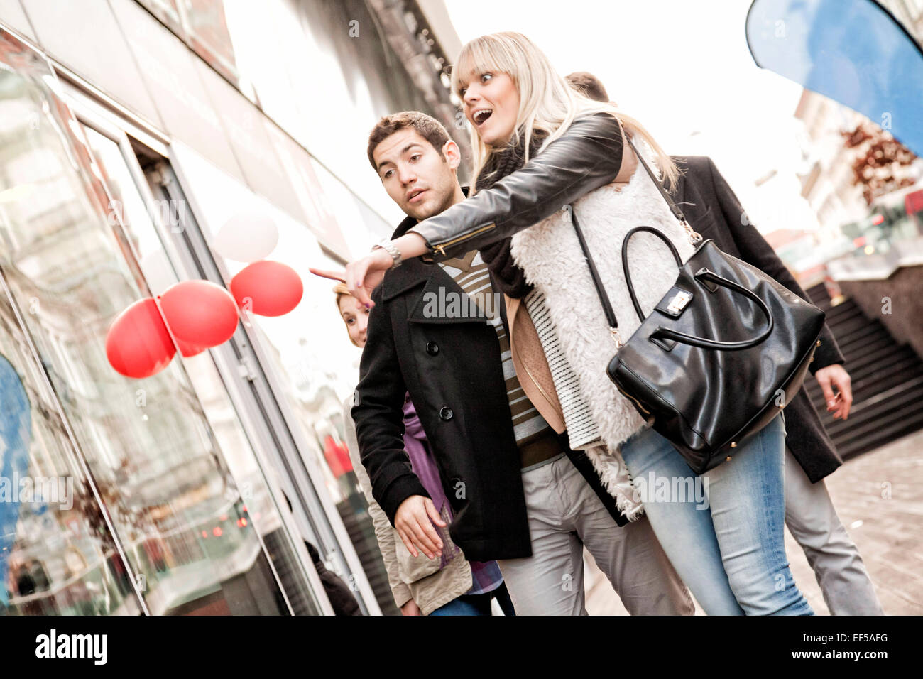 Group of friends looking at shop window - Stock Image
