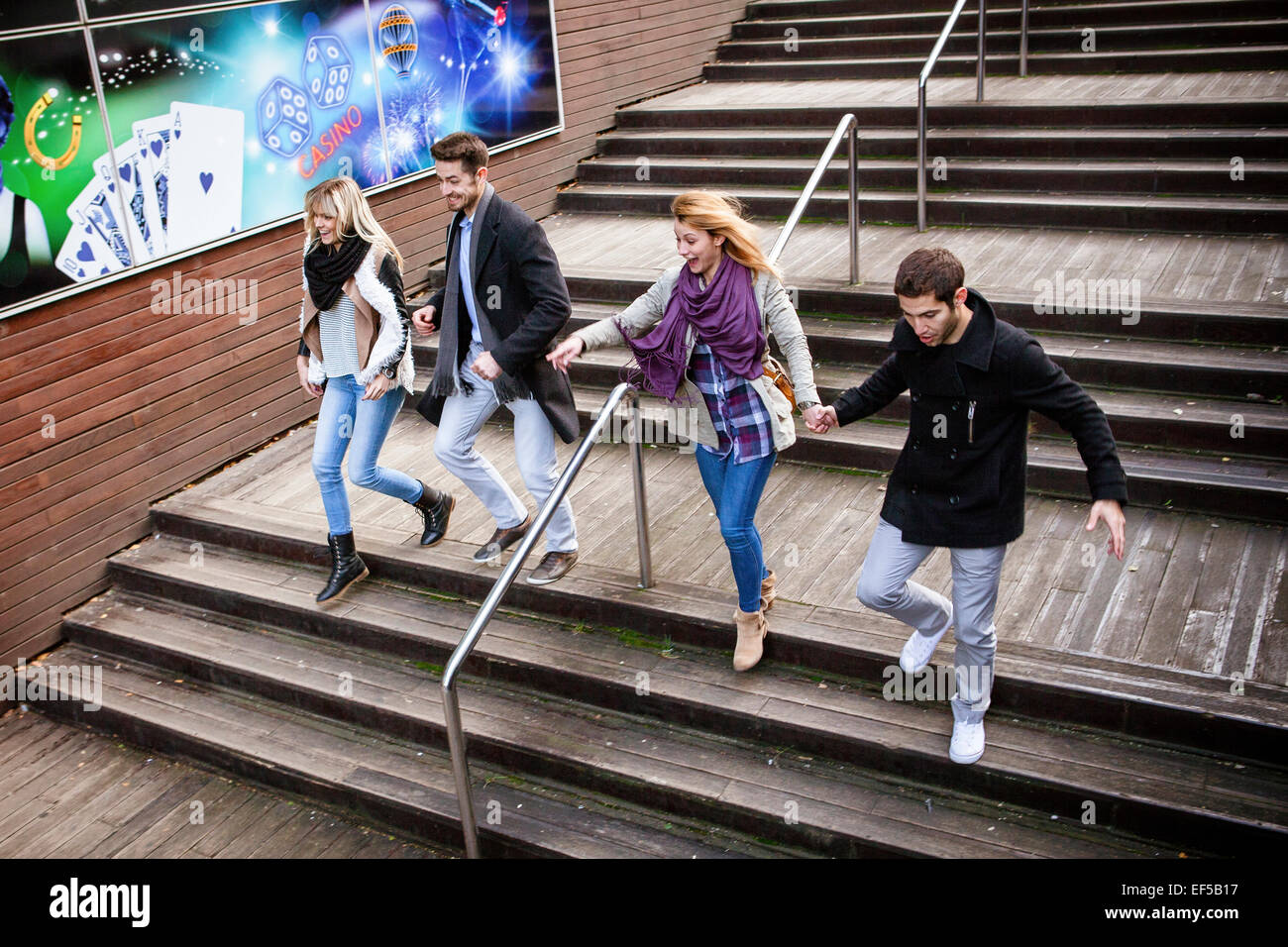 Group of friends walking down steps in town - Stock Image
