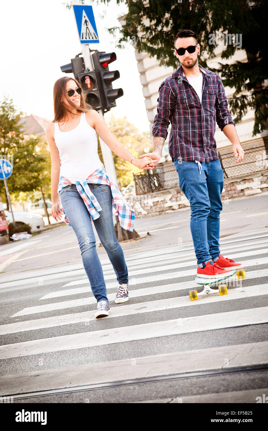 Young couple with skateboard crossing street - Stock Image