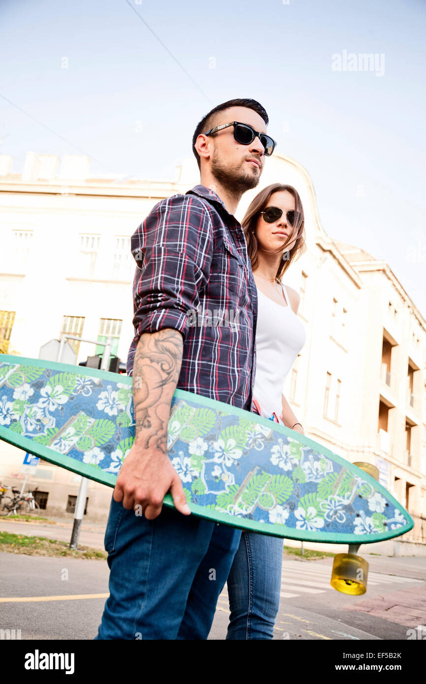 Young couple with skateboard walking in town - Stock Image