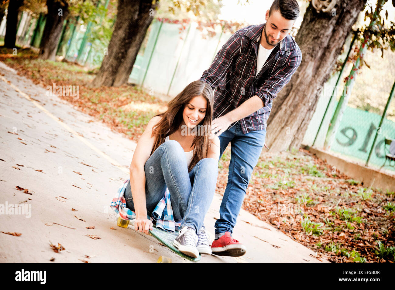 Young woman skateboarding, man supporting her - Stock Image