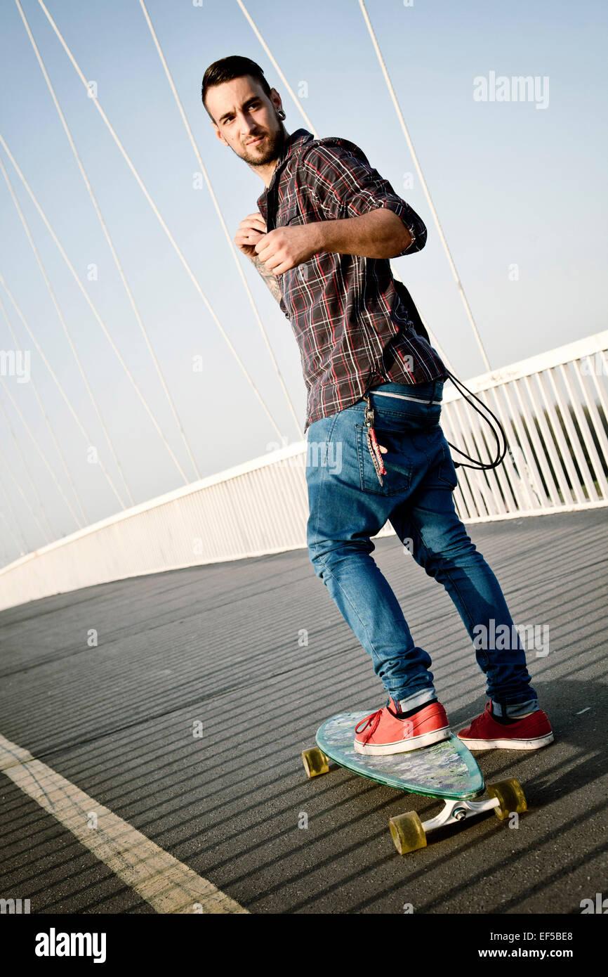 Young man skateboarding across bridge - Stock Image