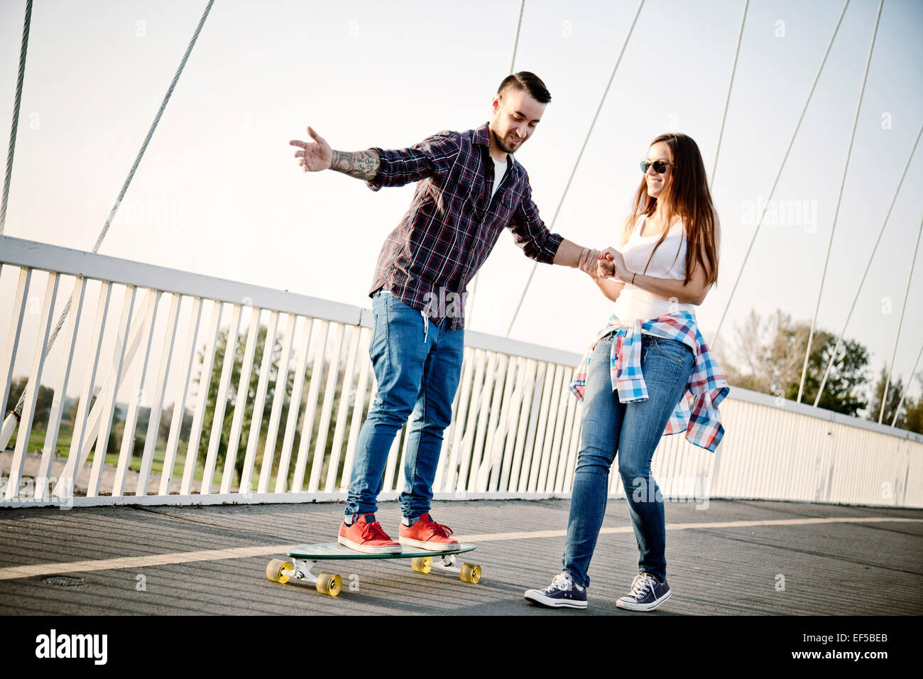 Young man balancing on skateboard, woman assisting - Stock Image