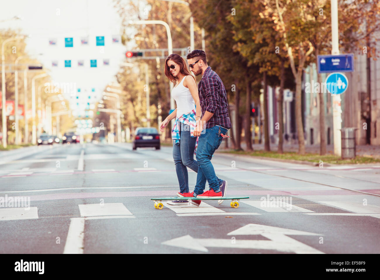Young couple skateboarding over zebra crossing - Stock Image