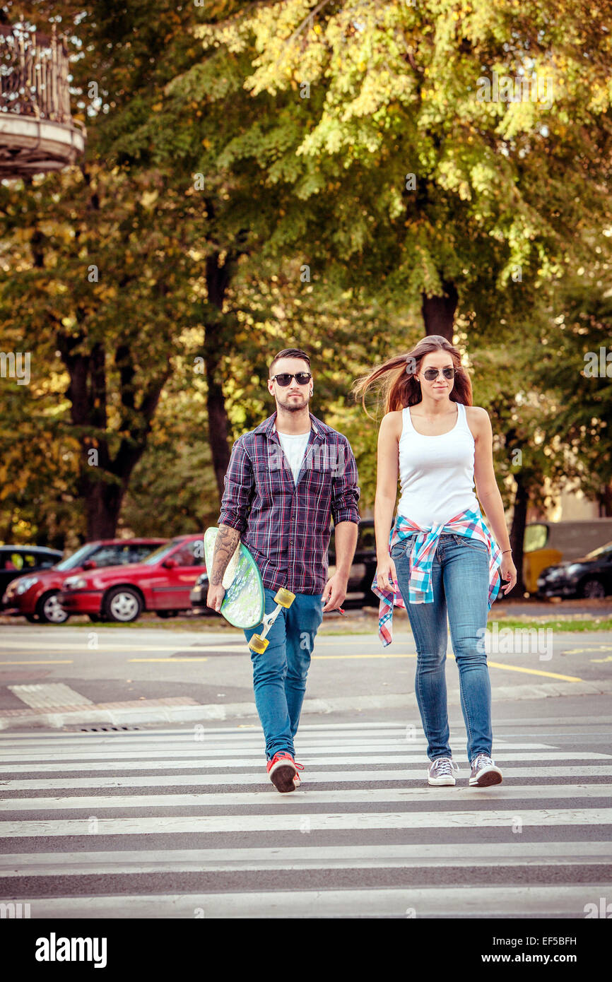Young couple with skateboard crossing city street - Stock Image