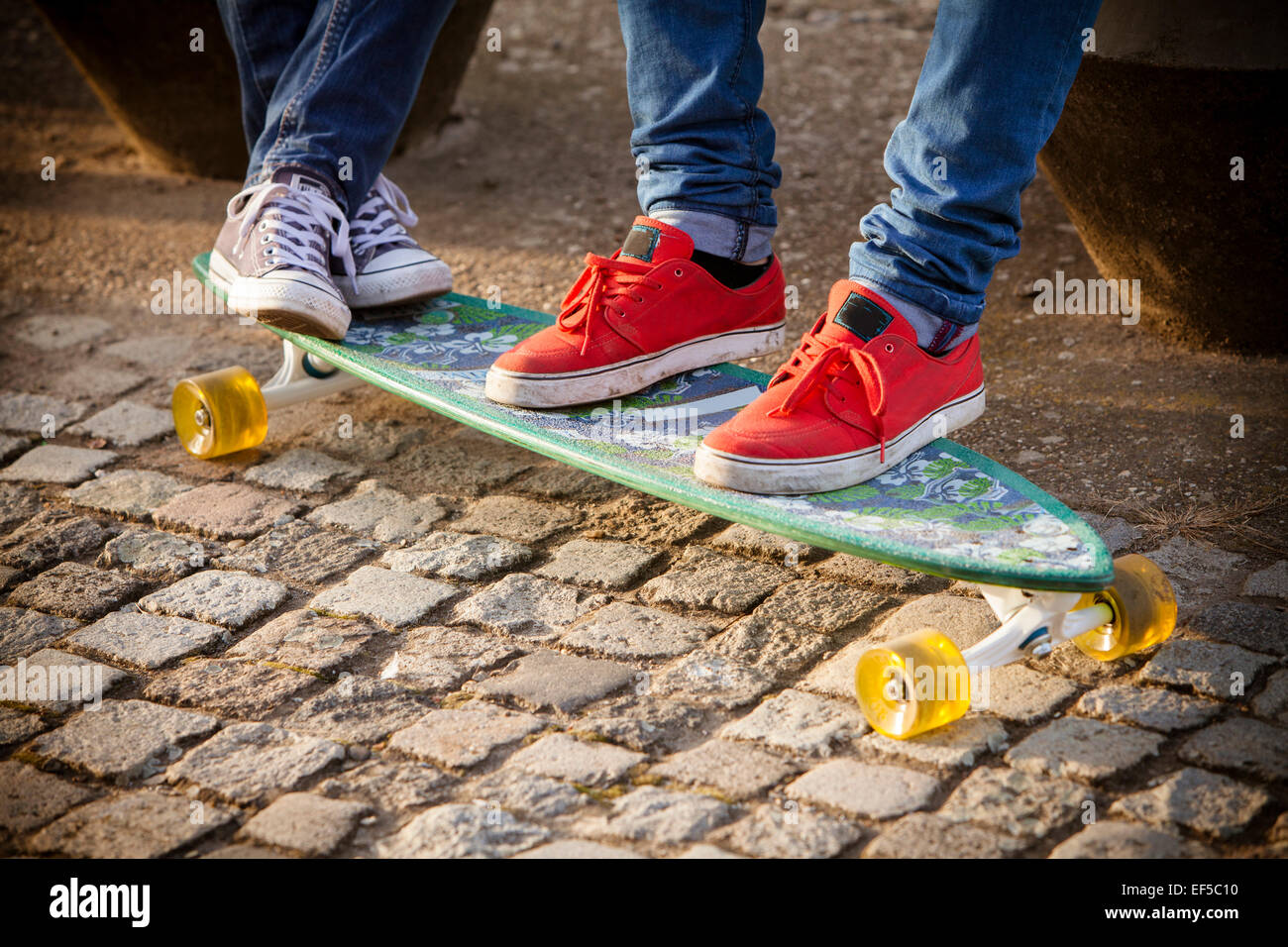 Sports shoes on skateboard - Stock Image
