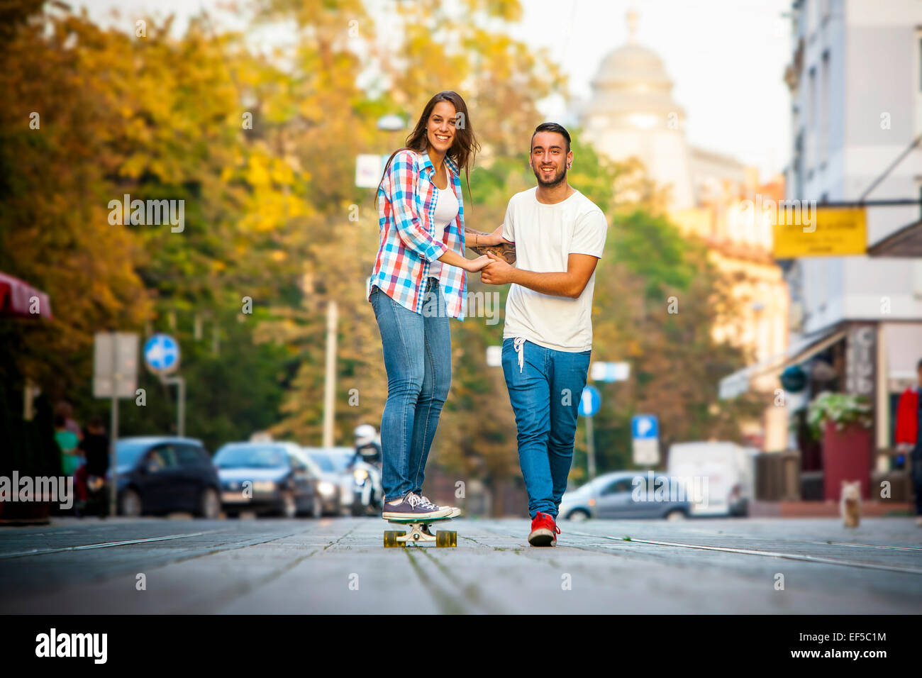 Young woman skateboarding on city street, man assisting - Stock Image