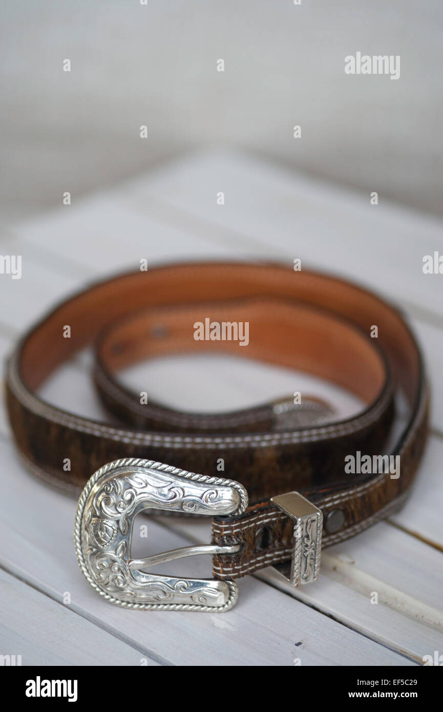 A belt with a silver buckle on a white wooden table Stock Photo