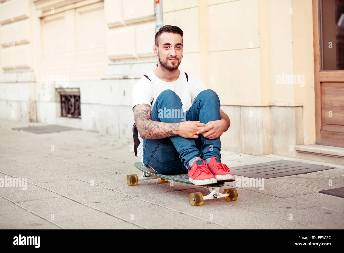 Young man with skateboard on sidewalk Stock Photo