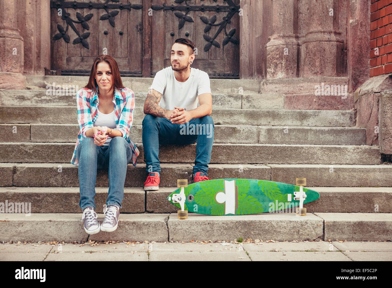 Young couple with skateboard taking a break on staircase Stock Photo