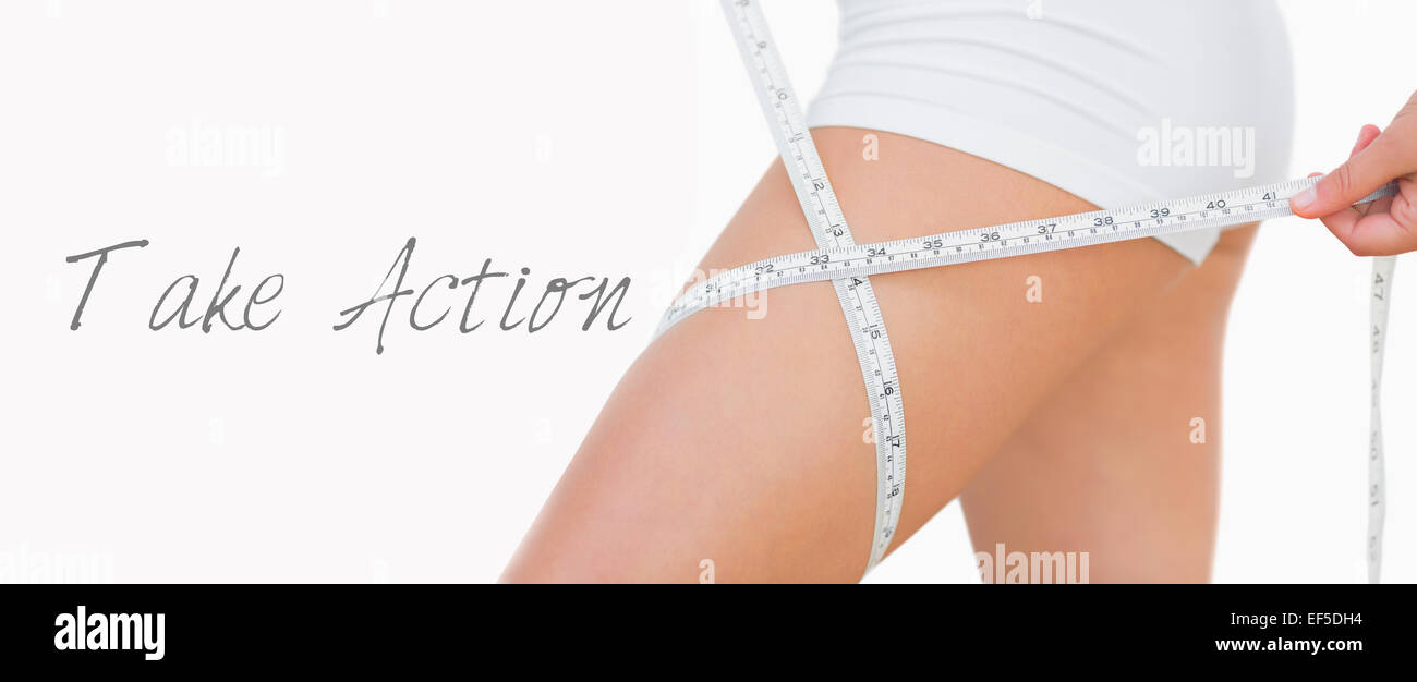 Midsection of woman measuring thigh - Stock Image