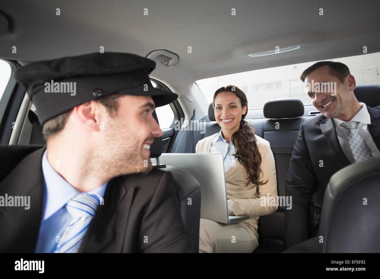 Handsome chauffeur smiling at clients - Stock Image