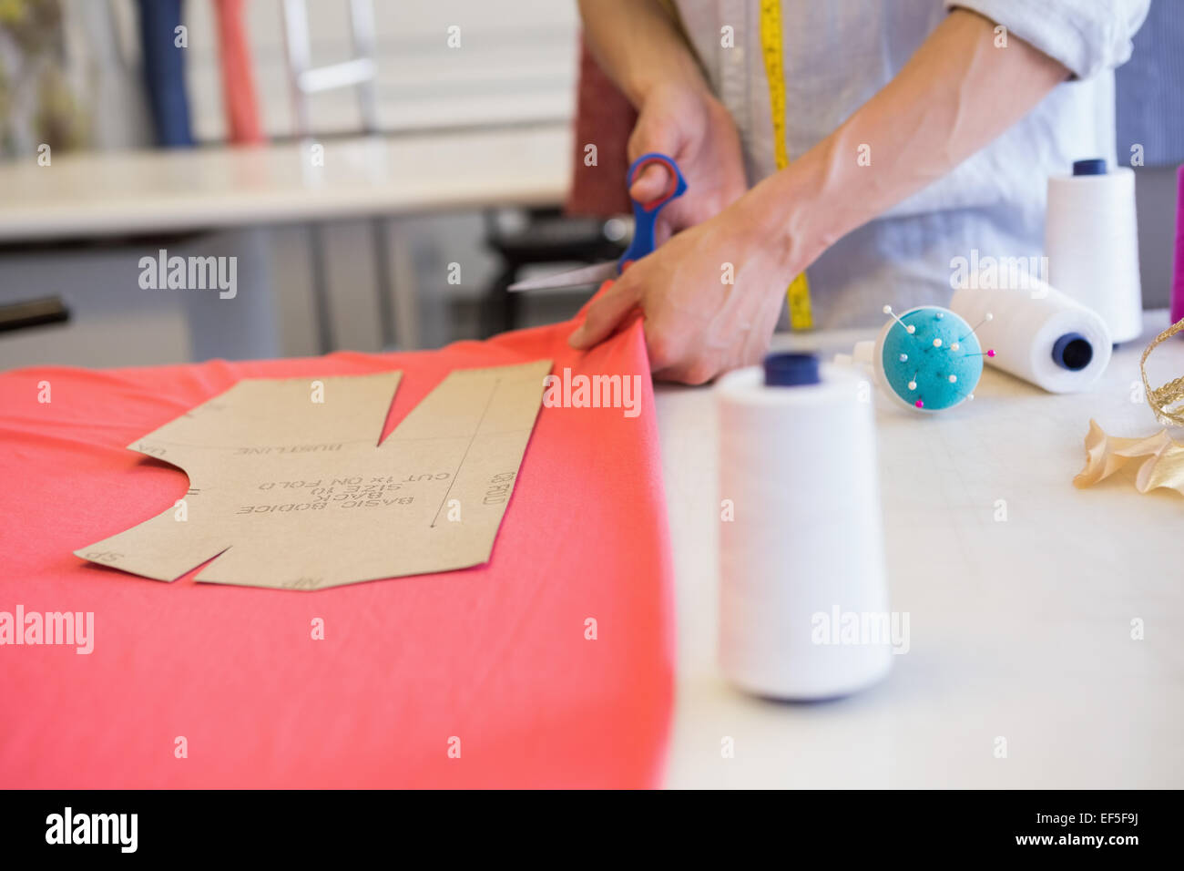 Student cutting fabric with pair of scissors - Stock Image