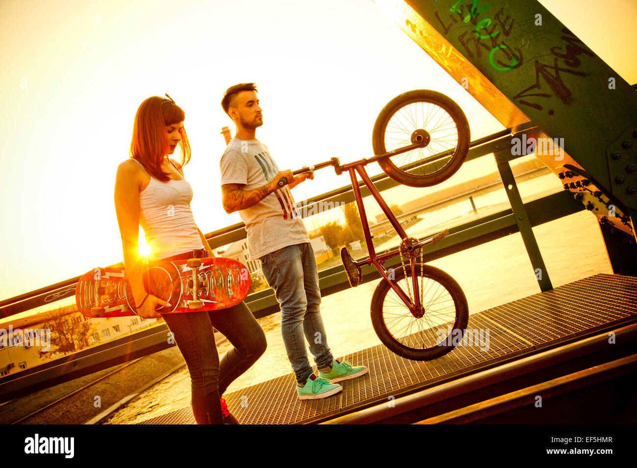 Young couple with skateboard and BMX bicycle outdoors - Stock Image