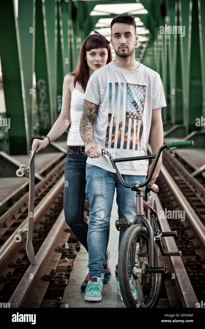 Young couple with skateboard and BMX bicycle outdoors Stock Photo