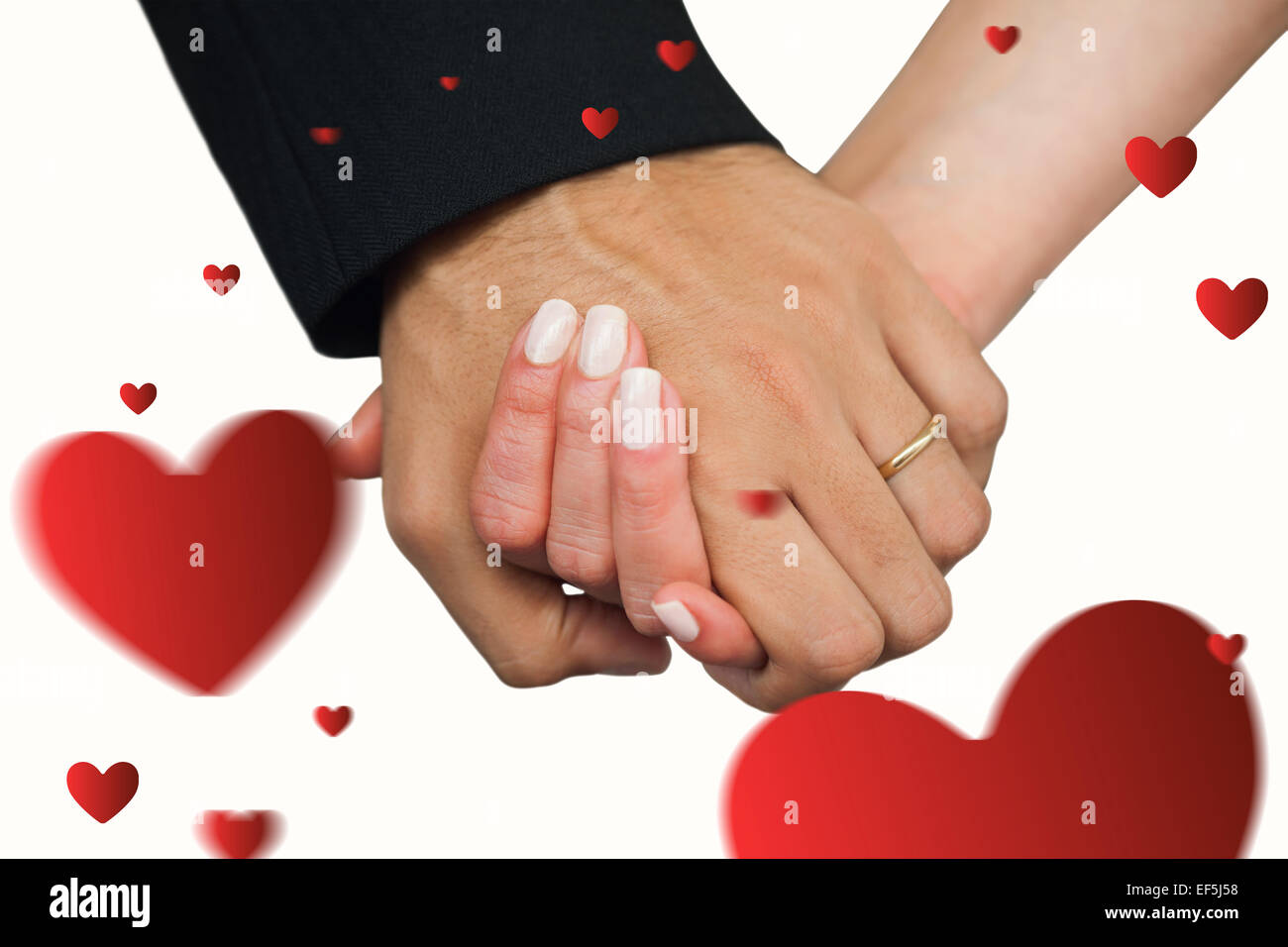 Composite image of newlyweds holding hands close up - Stock Image